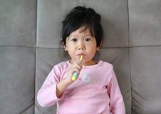桃红色的小女孩在沙发掠过的牙 库存照片