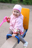 桃红色的小美丽的女孩坐跷跷板夏日 免版税库存图片