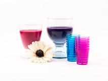 桃红色的构成和紫罗兰上色了鸡尾酒、蓝色和桃红色杯子和一朵花在白色背景 免版税图库摄影