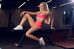 桃红色的白肤金发的妇女炫耀衣物坐健身房长凳 库存照片