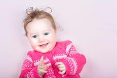 桃红色的逗人喜爱的女婴编织了有心脏样式的毛线衣 免版税库存照片