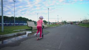 桃红色盖帽乘驾滑行车的小逗人喜爱的白肤金发的女孩在公园 股票录像