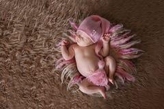 桃红色盖帽的嫩睡觉的新出生的婴孩 免版税库存图片