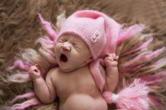 桃红色盖帽的甜新出生的婴孩打呵欠,并且舒展,醒来 免版税图库摄影