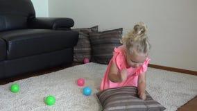 桃红色礼服命中枕头的俏丽的女孩孩子用在地板上的手在家 影视素材
