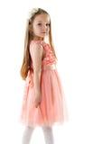 桃红色礼服和外缘的迷人的小女孩 免版税库存照片