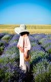 桃红色礼服和黑帽会议的美女在淡紫色领域,不看照相机 清楚的好日子 ?? ?treadled 免版税库存照片