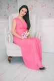 桃红色礼服坐的白色扶手椅子的深色的女孩有花花束的在他们的手上 免版税库存图片