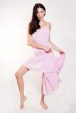 桃红色礼服摆在的全长深色的女性 免版税库存图片