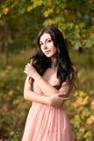 桃红色礼服的可爱的肉欲的妇女 秋天,秋天 免版税库存照片