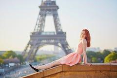 桃红色礼服的在埃佛尔铁塔附近,巴黎女孩 免版税库存照片