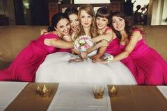 桃红色礼服的女傧相倾斜给一个俏丽的新娘坐Th 免版税库存照片