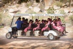 桃红色礼服的女小学生,去在长的电动车 免版税库存照片