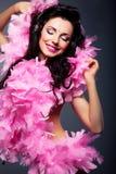 桃红色礼服的妇女听到音乐的 免版税图库摄影