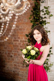 桃红色礼服的妇女有在砖墙背景的花的 库存照片