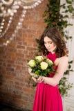 桃红色礼服的妇女有在砖墙背景的花的 免版税库存照片
