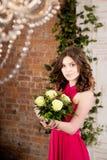 桃红色礼服的妇女有在砖墙背景的花的 免版税库存图片
