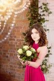 桃红色礼服的妇女有在砖墙背景的花的 免版税图库摄影