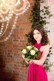 桃红色礼服的妇女有在砖墙背景的花的 库存图片