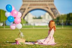 桃红色礼服的妇女有束的气球有野餐在埃佛尔铁塔附近在巴黎 免版税库存照片