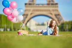 桃红色礼服的妇女有束的气球有野餐在埃佛尔铁塔附近在巴黎 库存照片