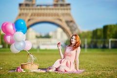 桃红色礼服的妇女有束的气球有野餐在埃佛尔铁塔附近在巴黎 库存图片