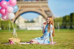 桃红色礼服的妇女有束的气球有野餐在埃佛尔铁塔附近在巴黎 免版税库存图片