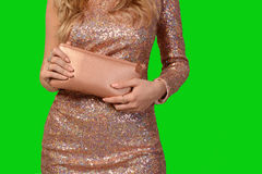 桃红色礼服的妇女有衣服饰物之小金属片的在手上拿着一台传动器在绿色背景 免版税库存照片
