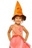 桃红色礼服的小女孩和万圣夜帽子 图库摄影