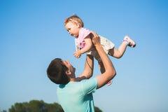 桃红色礼服的小女孩在她的父亲的手上 免版税库存照片