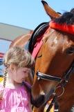桃红色礼服的小美丽的女孩在棕色马附近站立 免版税库存照片
