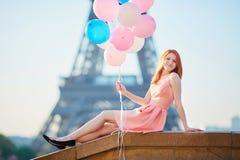 桃红色礼服的少妇有束的气球在埃佛尔铁塔附近的巴黎 免版税库存照片
