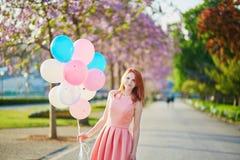 桃红色礼服的少妇有束的气球在巴黎 免版税库存照片