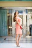 桃红色礼服的少妇走在商店的 库存图片