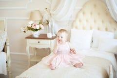 桃红色礼服的微笑的小女婴在床上 免版税库存图片