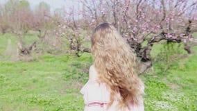 桃红色礼服的白肤金发的女孩在繁茂花园里走 股票录像
