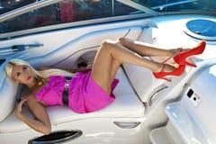 桃红色礼服的白肤金发的妇女在小船,夏天 免版税库存照片