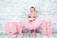 桃红色礼服的美丽和逗人喜爱的女孩在词一的背景,哭泣在她的第一个生日 情感子项 免版税库存图片