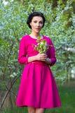 桃红色礼服的美丽的梦想的妇女在春天樱桃庭院里 免版税库存图片