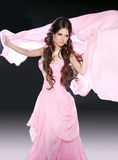 桃红色礼服的美丽的深色的女孩有吹的组织织品的 免版税图库摄影