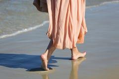 桃红色礼服的赤足走在湿沙子的一名妇女的腿,索波特,波兰 库存照片