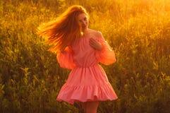 桃红色礼服的跳舞的美丽的女孩在领域,太阳背后照明, s 库存图片