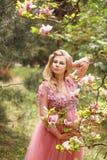 桃红色礼服花的美丽的孕妇接触站立在开花的木兰树附近的手腹部 免版税图库摄影