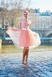 桃红色礼服跳舞的少妇在河塞纳河附近的巴黎 免版税库存照片