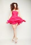 桃红色礼服跳跃的年轻迷人的女性 库存照片