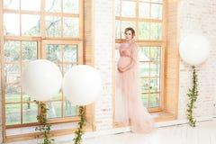桃红色礼服身分在窗口基石和握的充满爱她的腹部快乐的美丽的怀孕的年轻女人 免版税库存照片