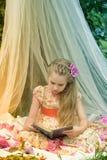 桃红色礼服阅读书的女孩 免版税库存图片