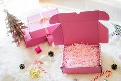 桃红色礼物盒打开与明亮的灯、糖果和星的弓丝带 免版税库存照片