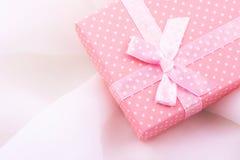 桃红色礼物盒栓与与弓的缎丝带在精美白色织品背景,浪漫,华伦泰,母亲` s天,圣诞节 库存图片