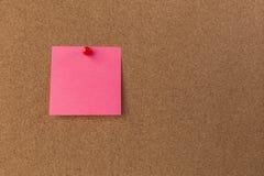 桃红色空白的稠粘的笔记红色被别住入棕色corkboard 关闭 库存图片